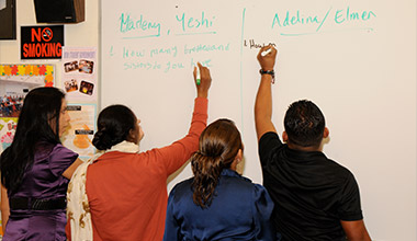 Photo of three adults writing on a whiteboard.